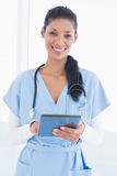Smiling doctor using tablet Stock Photo