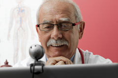 Smiling Doctor using webcam Royalty Free Stock Photos