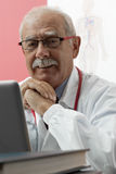 Smiling Doctor using webcam. Senior doctor speaking with patient through webcam Stock Image