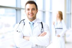 Smiling doctor waiting for his team while standing upright Royalty Free Stock Image