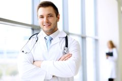 Smiling doctor waiting for his team while standing upright Stock Photography