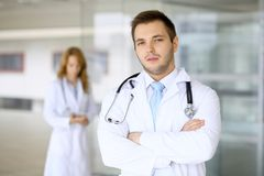 Smiling doctor waiting for his team while standing upright Stock Photo