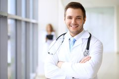 Smiling doctor waiting for his team while standing upright.  Stock Images