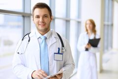 Smiling doctor waiting for his team while standing upright Stock Images