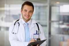 Smiling doctor waiting for his team while standing upright Royalty Free Stock Photo