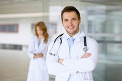 Smiling doctor waiting for his team while standing upright Royalty Free Stock Photos