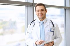 Smiling doctor waiting for his team while standing upright Stock Image