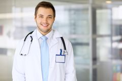Smiling doctor waiting for his team while standing upright Royalty Free Stock Photography