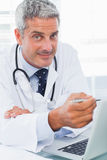 Smiling doctor watching something on his laptop Royalty Free Stock Image