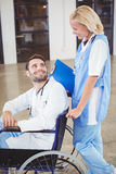 Smiling doctor on wheelchair interacting with female colleague Royalty Free Stock Photo