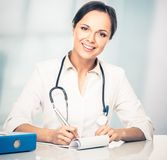Smiling doctor woman behind table Royalty Free Stock Photos