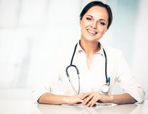 Smiling doctor woman behind table Stock Images