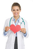 Smiling doctor woman holding heart shape paper Royalty Free Stock Photos