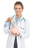 Smiling doctor woman putting dollars banknote in piggy bank Royalty Free Stock Image