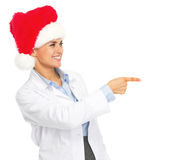 Smiling doctor woman in santa hat pointing on copy space Royalty Free Stock Images