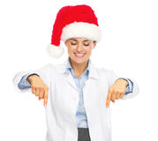 Smiling doctor woman in santa hat pointing down on copy space Royalty Free Stock Photography