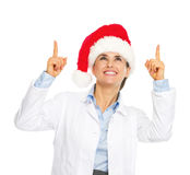Smiling doctor woman in santa hat pointing up on copy space. Isolated on white Royalty Free Stock Photo