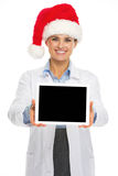 Smiling doctor woman in santa hat showing tablet pc blank screen Stock Photos