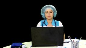 Smiling doctor working at the computer. Alpha stock video