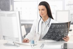 Smiling doctor working at desk stock image