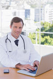 Smiling doctor working on his laptop Royalty Free Stock Photo