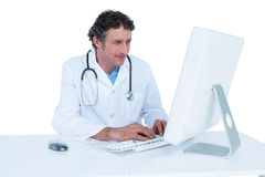 Smiling doctor working on his laptop Stock Photo
