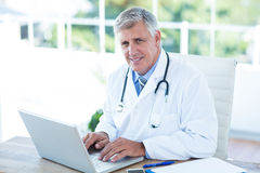 Smiling doctor working on laptop at his desk Royalty Free Stock Images
