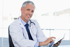 Smiling doctor working with a tablet computer Stock Photography