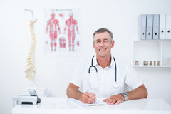 Smiling doctor writing on clipboard at his desk Royalty Free Stock Photography