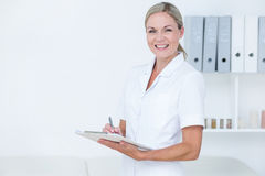 Smiling doctor writing on clipboard Stock Photos