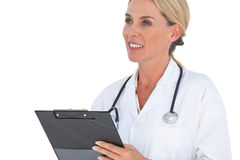 Smiling doctor writing on a clipboard Stock Image