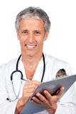Smiling doctor writing documents Stock Photos