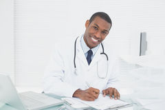 Smiling doctor writing a note at medical office Royalty Free Stock Images
