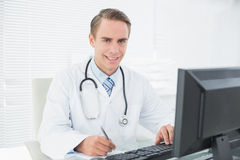Smiling doctor writing note while using computer at medical office Royalty Free Stock Images