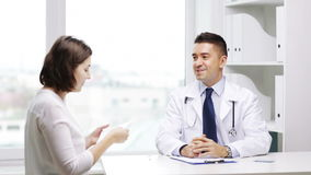 Smiling doctor and young woman meeting at hospital