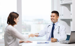 Smiling doctor and young woman meeting at hospital Stock Images