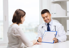 Smiling doctor and young woman meeting at hospital Royalty Free Stock Photos