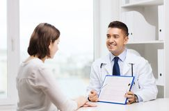 Smiling doctor and young woman meeting at hospital Stock Photos