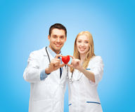 Smiling doctors cardiologists with heart. Healthcare and medical concept - two young doctors cardiologists with heart royalty free stock photo