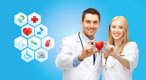 Smiling doctors cardiologists with small red heart Royalty Free Stock Photos