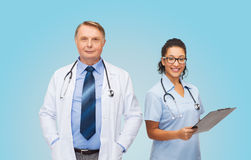 Smiling doctors with clipboard and stethoscopes Stock Photos