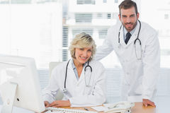 Smiling doctors with computer at medical office Stock Images
