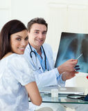 Smiling doctors examining an x-ray Royalty Free Stock Image