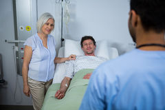 Smiling doctors interacting with each other. While patient lying on bed Stock Images