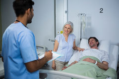 Smiling doctors interacting with each other. While patient lying on bed Royalty Free Stock Image
