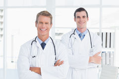 Smiling doctors looking at camera with arms crossed Royalty Free Stock Photo