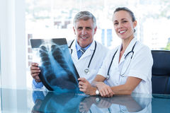 Smiling doctors looking at camera and holding xray Stock Photo