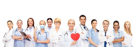 Smiling doctors and nurses with red heart. Healthcare and medicine concept - smiling doctors and nurses with red heart royalty free stock image
