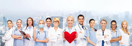 Smiling doctors and nurses with red heart. Healthcare and medicine concept - smiling doctors and nurses with red heart stock images