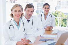 Smiling doctors posing at their desk Royalty Free Stock Images